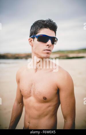 Ritratto di shirtless giovane uomo sulla spiaggia indossando occhiali da sole Foto Stock