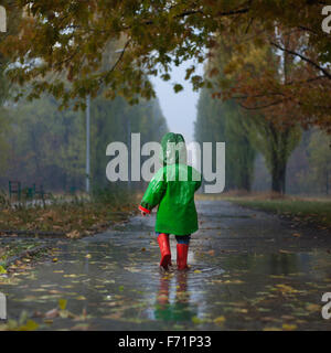 Baby camminando in autunno piovoso park Foto Stock