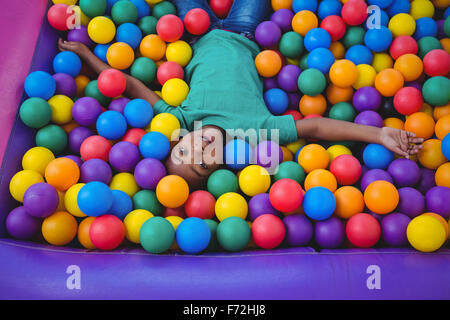 Carino il ragazzo sorridente in spugna piscina di palline Foto Stock