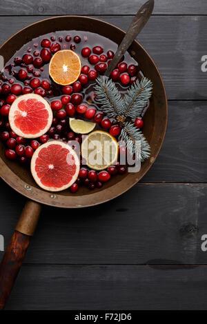 Inverno caldo punch,sangria,toddy o vin brulé con limone e pompelmo,mandarino, calce e cranberry in età di ottone Foto Stock