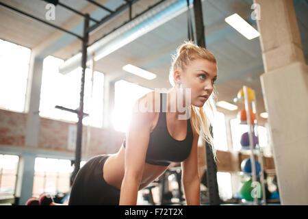 Piscina colpo di giovane donna fitness facendo spingere ups in palestra. Femmina caucasica di lavoro nel club salute. Foto Stock