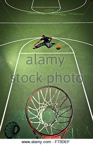 Un giocatore di basket si estende davanti a un gioco. Foto Stock