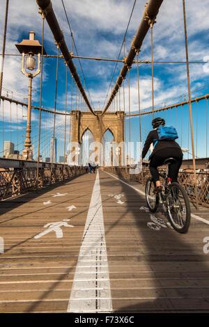 Ciclista in sella la sua bici sul ponte di Brooklyn, New York, Stati Uniti d'America Foto Stock