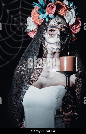 Messico - Dia de Muertos. La Calavera Catrina holding - candela tradizionale messicano scheletro femminile figura che simboleggia la celebra Foto Stock