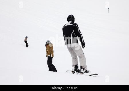 Gli appassionati di snowboard imbarco verso il basso coperto di neve piste da sci nelle Alpi austriache. St Anton Foto Stock
