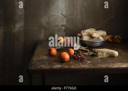 Natura morta con frutta e mais in un recipiente di alluminio su una tavola di legno vecchio tavolo Foto Stock