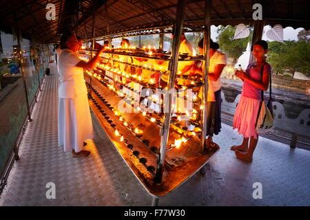 Sri Lanka, Kandy - pellegrini si accendono le candele nel tempio del Dente, Sri Dalada Maligawa, Patrimonio Mondiale Foto Stock