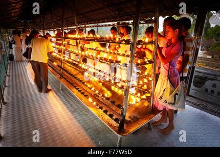 Sri Lanka, Kandy - pellegrini si accendono le candele nel tempio del Dente, Sri Dalada Maligawa, santuario buddista, Foto Stock