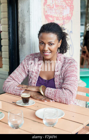 Donna seduta al cafè sul marciapiede Foto Stock