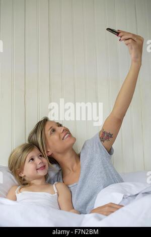Madre e figlia in posa per selfie Foto Stock