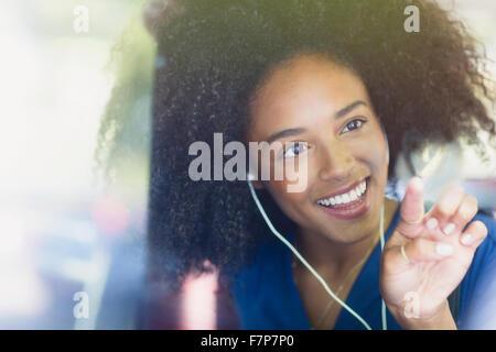 Donna sorridente con afro e cuffie cuore di disegno-forma sulla finestra del bus Foto Stock