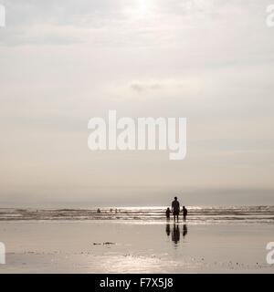 Silhouette di un uomo in piedi sul mare con due bambini Foto Stock