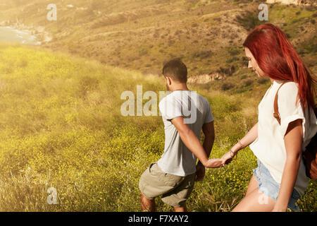 Colpo all'aperto di coppia giovane godendo sulla loro vacanza, percorrendo a piedi un picco tenendo le mani. Coppia Foto Stock