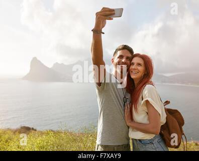 Allegro una giovane coppia in vacanza facendo selfie con smart phone. Coppia giovane dalla baia di prendere un ritratto Foto Stock