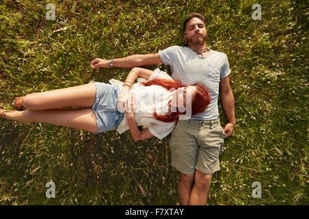 Giovane uomo e donna sdraiata sul prato dormire. Vista aerea della coppia giovane appoggiato insieme sull'erba. Foto Stock