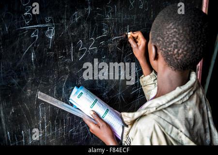 Un giovane keniota bambino di strada figure scrive sulla lavagna di un centro di salvataggio in Kitale, Kenya Foto Stock