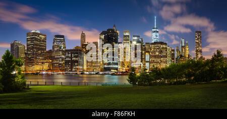 Vista serale di Lower Manhattan grattacieli illuminati attraverso il Ponte di Brooklyn Park. Manhattan Financial District di New York City Foto Stock