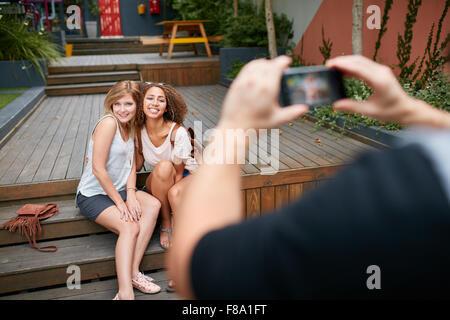 Due giovani donna seduta insieme che posano per una foto essendo tenuto da un loro amico. L'uomo prendendo fotografie Foto Stock