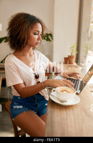 Piscina colpo di giovane donna informale seduti in un caffè utilizzando laptop. Ragazza africana navigando in internet Foto Stock