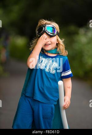 Un piccolo pre-teen boy in una casa fatta di costume e occhiali vestito e giocare all'aperto presso essendo Mini Foto Stock