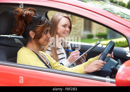 Giovane donna con lezione di guida con istruttore femmina Foto Stock