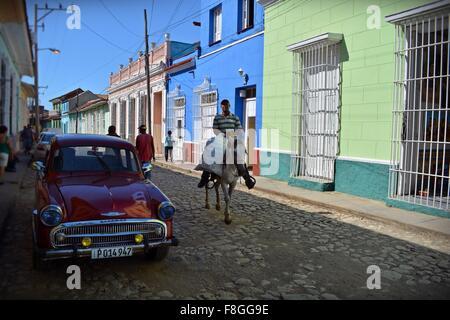 Cavaliere e i pedoni a camminare su un parzialmente ombreggiata strada di ciottoli in una colorata Trinidad Sancti Foto Stock