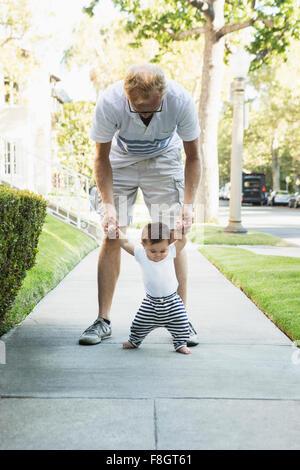 Padre aiutando baby figlio camminare sul marciapiede Foto Stock