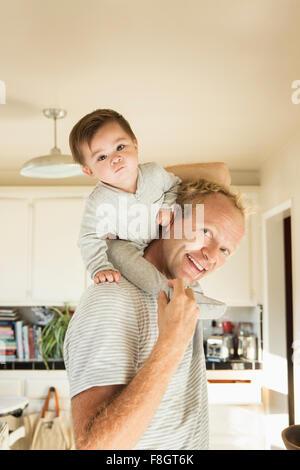 Padre bambino portando figlio sulle spalle Foto Stock