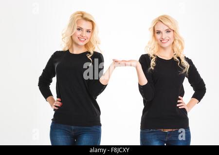 Ritratto di un felice sorelle gemelli azienda copyspace sulle palme isolate su uno sfondo bianco Foto Stock