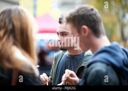 Un gruppo di giovani adulti di mangiare cibo da asporto, all'aperto Foto Stock