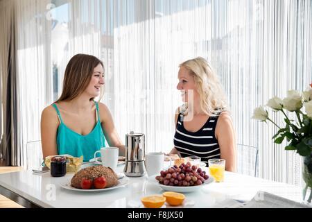 La donna seduta al tavolo da pranzo godendo di una colazione continentale insieme, faccia a faccia sorridente Foto Stock