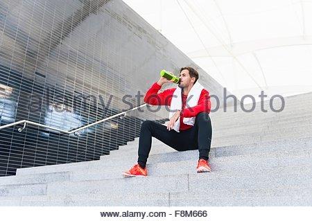 Giovane maschio runner di bere acqua in bottiglia sulla scalinata della città Foto Stock