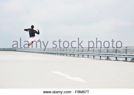 Vista posteriore del giovane maschio runner salti di gioia sul parcheggio tetto Foto Stock