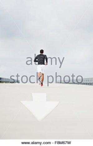 Vista posteriore del giovane maschio runner in esecuzione sul parcheggio tetto Foto Stock