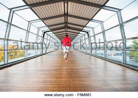 Vista posteriore del giovane maschio runner in esecuzione in passerella Foto Stock