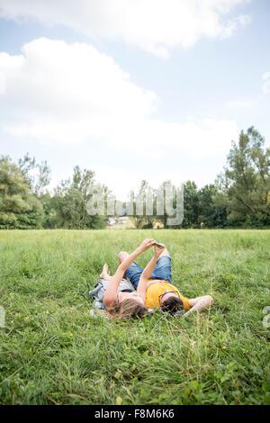 Coppia giovane giacente su erba in campo, tenendo autoritratto utilizza lo smartphone