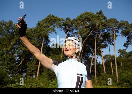 Coppia ciclista tenendo selfie accanto a forest Foto Stock