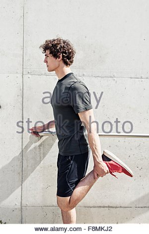 Giovane maschio runner stretching gambe in città Foto Stock