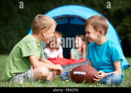 Due ragazzi parlando e giocando con il football americano sul viaggio di campeggio Foto Stock