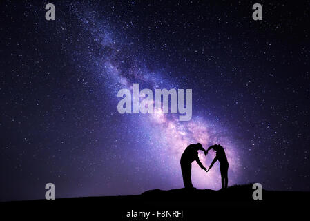 L uomo e la donna tenendo le mani in forma di cuore sullo sfondo della Via Lattea Foto Stock