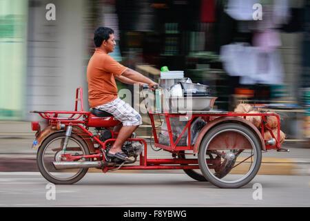 Il panning fotografia immagine di un uomo tailandese accelerando lungo una strada di città Foto Stock
