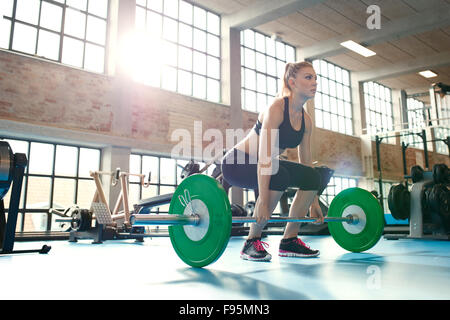 Determinata e forte donna fitness allenamento con i pesi pesanti nel fitness club. Caucasian atleta femminile fare sollevamento pesi e