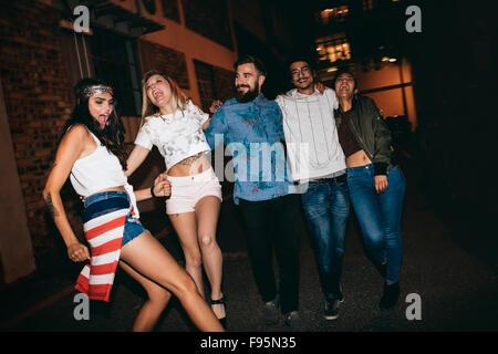 I giovani allegri insieme a piedi di notte e divertirsi. Gruppo multirazziale di amici appendere fuori la sera. Foto Stock