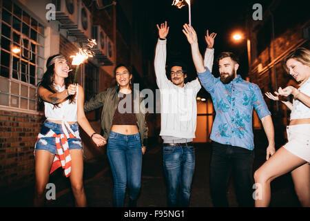 Ritratto di felice giovani amici per celebrare il capodanno con botti di notte. Migliori amici appendere fuori a Foto Stock