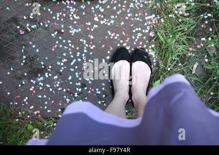 Sezione bassa della donna che indossa scarpe permanente sulla coriandoli strada coperta Foto Stock