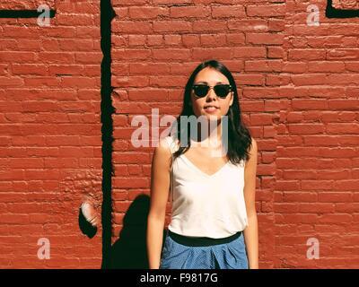Ritratto di giovane e bella donna in piedi contro rosso muro di mattoni Foto Stock