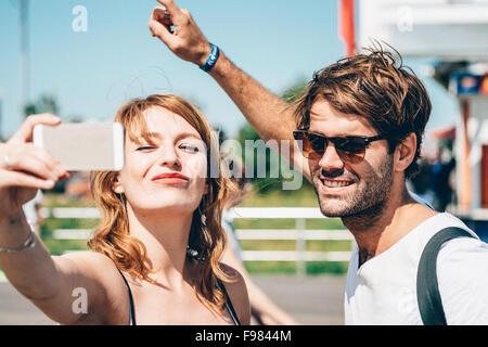 Happy amici facendo clic Selfie su Smart Phone permanente, mentre all'aperto Foto Stock