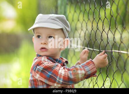Piccolo Grazioso baby boy guardando attraverso la recinzione Foto Stock