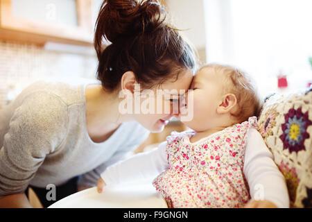 Giovane madre e la sua piccola figlia avente insieme per la prima colazione Foto Stock