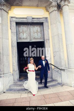 Sposa e lo sposo a piedi fuori della chiesa tenendo le mani Foto Stock